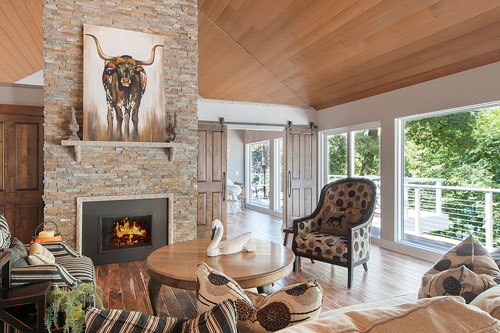 A rustic living-space with stone fireplace, vault ceilings, and hickory flooring