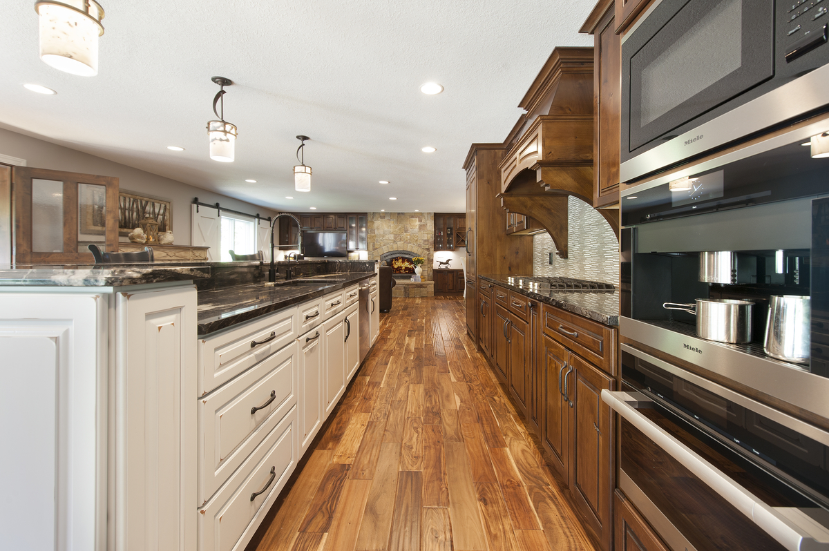 Rustic wide plank wood flooring unites contrasting cabinetry