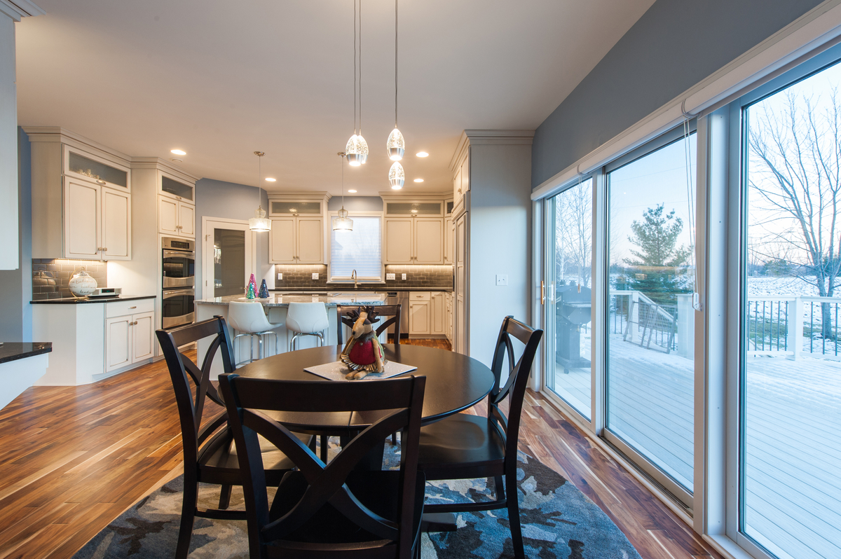 Open transition from dining to kitchen with inviting wide plank ash wood flooring throughout