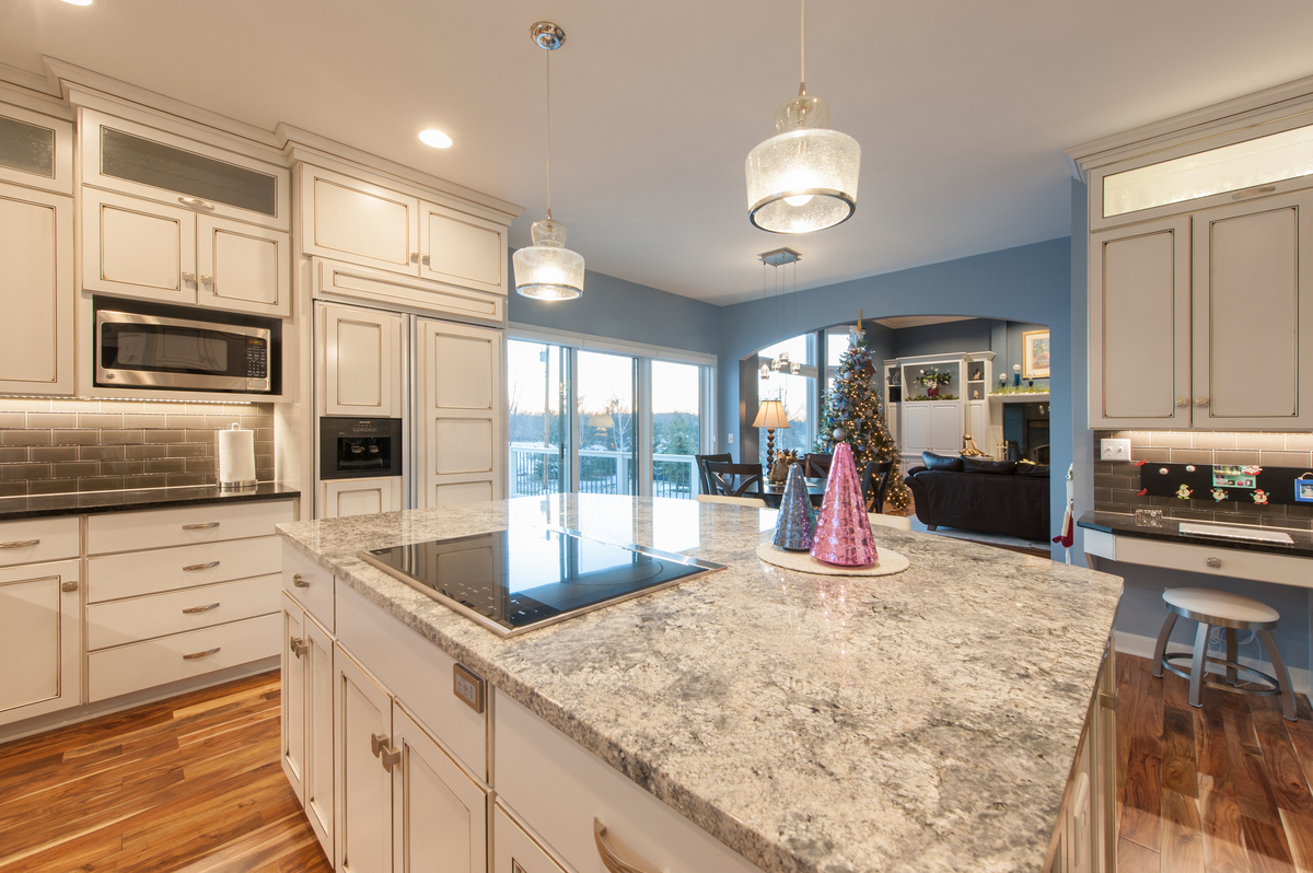 Contemporary finishes include glass cooktop, granite countertops and subway tile backsplash