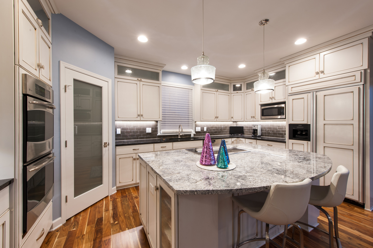 Gently distressed white cabinetry offers a vintage feel