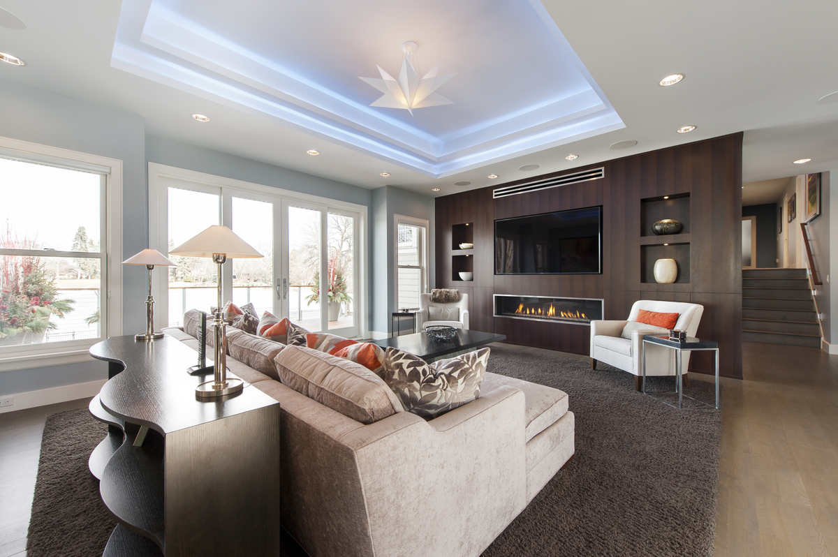 Contemporary living-space with medium wood floors, open floor plan and tray ceiling.