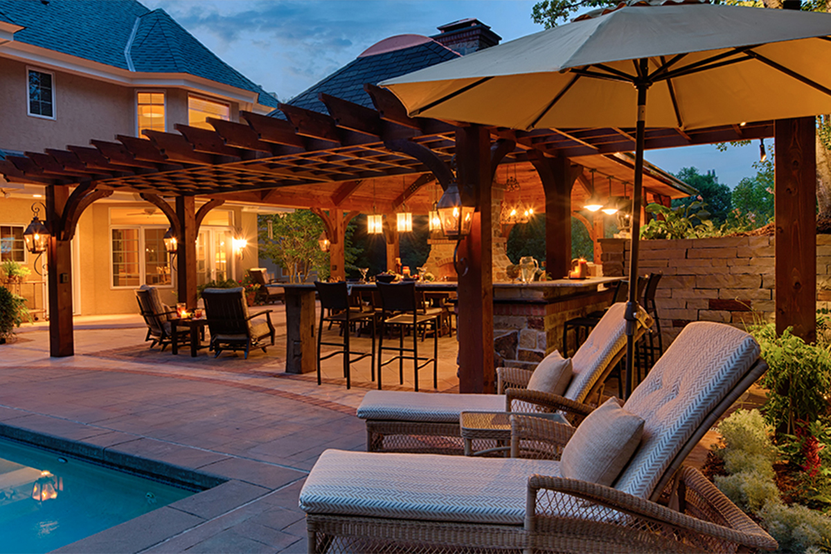 Illuminated poolside pergola with outdoor kitchen for dining and entertaining