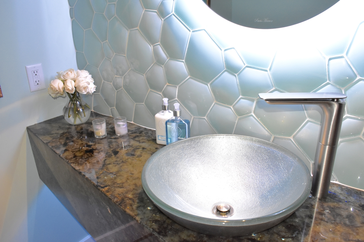 vessel sink rests on marble slab vanity top