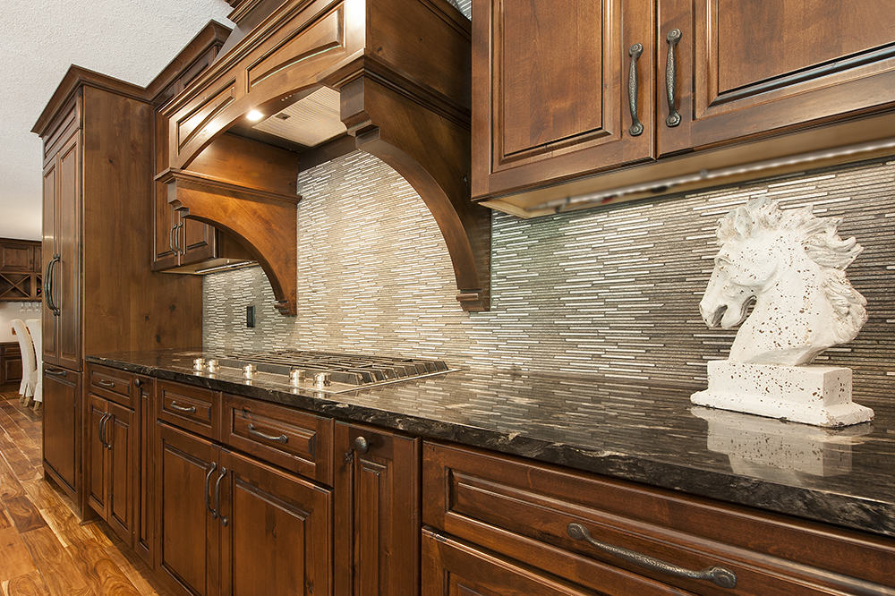 Impressive rustic alder dark glazed cabinetry with hammered pulls